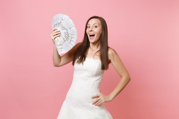 Mulher empolgada em um vestido de renda branca segurando um monte de dólares em dinheiro