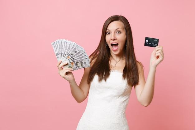 Mulher empolgada em um vestido de renda branca segurando um pacote de muitos dólares, dinheiro em espécie e cartão de crédito