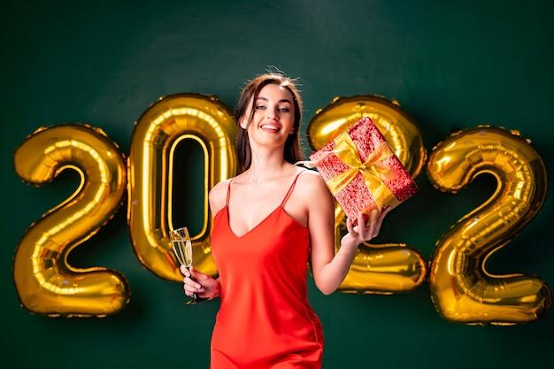 Mulher empolgada em um vestido vermelho segurando uma caixa vermelha de presente e uma taça de champanhe. Foto Premium