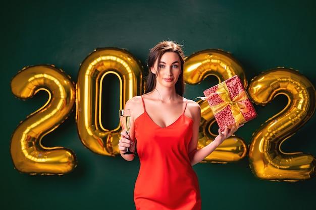 Mulher empolgada em um vestido vermelho segurando uma caixa vermelha de presente e uma taça de champanhe.