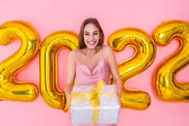 Mulher empolgada segurando caixa de presente isolada na celebração de ano novo de balões de ar de fundo rosa