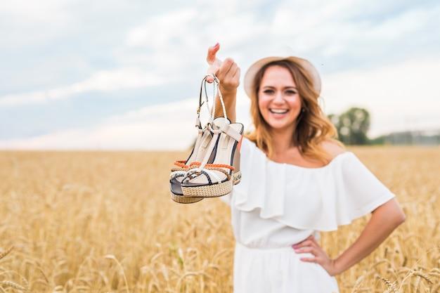 Mulher empolgada segurando sapatos novos que encontrou à venda.