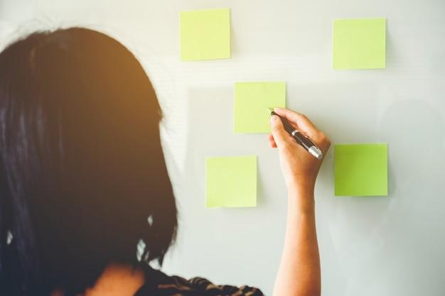 Mulher empreendedor colocando suas idéias no planejamento post-it no novo projeto de negócios