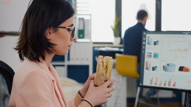 Mulher empreendedora comendo sanduíche saboroso durante a hora do almoço para viagem trabalhando em gráficos financeiros