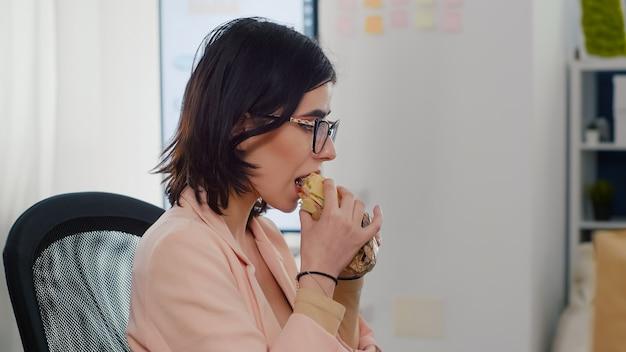 Mulher empreendedora comendo sanduíche saboroso no intervalo do trabalho, trabalhando em empresa de negócios