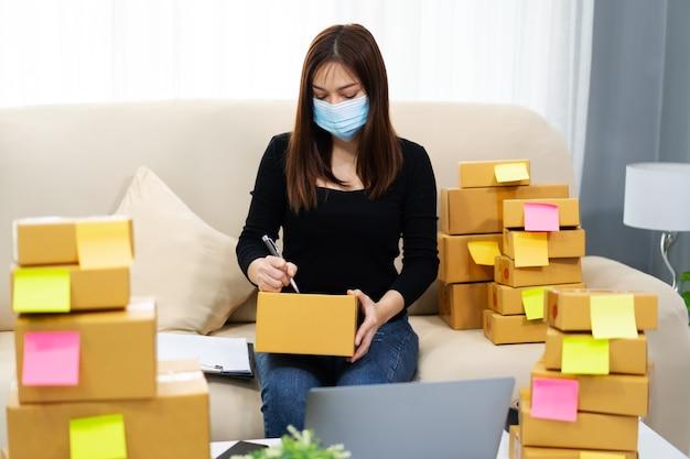 Mulher empreendedora prepara caixa de encomendas para entrega ao cliente no escritório de casa, ela usa uma máscara facial para proteger a pandemia de coronavírus