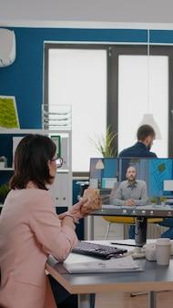 Mulher empreendedora sentada à mesa no escritório da empresa, comendo sanduíche durante conferência de videochamada online ...