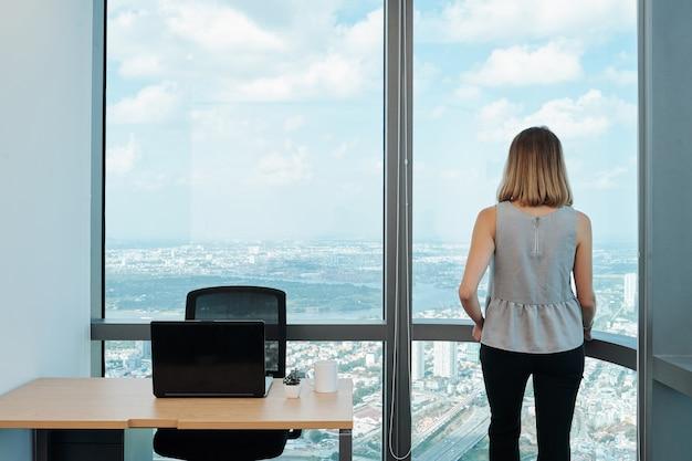Mulher empreendedora sonhadora olhando para a cidade grande