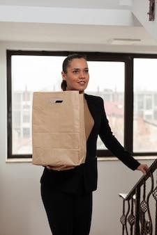 Mulher empreendedora subindo escadas no escritório de uma empresa startup segurando um pedido de comida para viagem