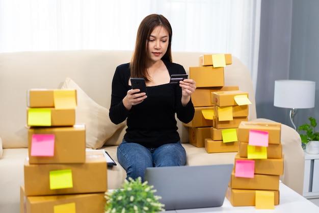 Mulher empreendedora usando smartphone com cartão de crédito no escritório doméstico