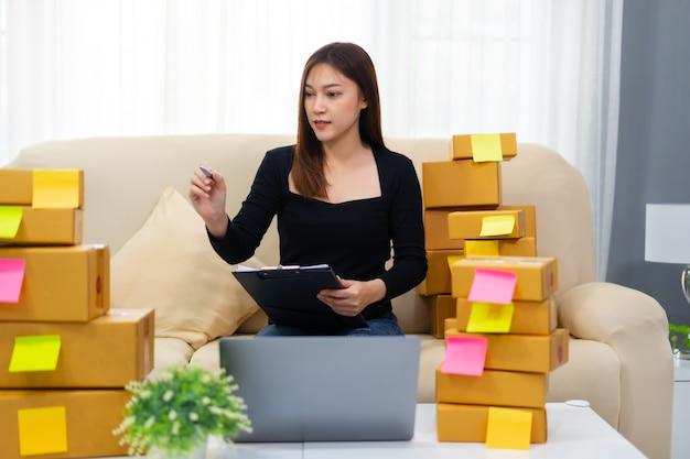 Mulher empreendedora verificando e escrevendo o pedido para entrega ao cliente, uma pme on-line no escritório doméstico