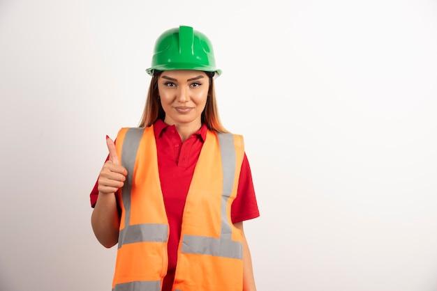 Mulher empregada em um colete e capacete protetor em fundo branco.