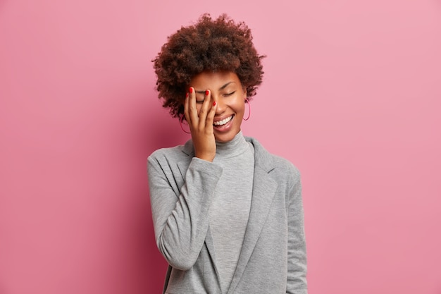 Mulher empresária de pele escura radiante ri positivamente, fica de olhos fechados, ri de piada engraçada, faz cara de palma, vestida com elegância, mostra dentes brancos