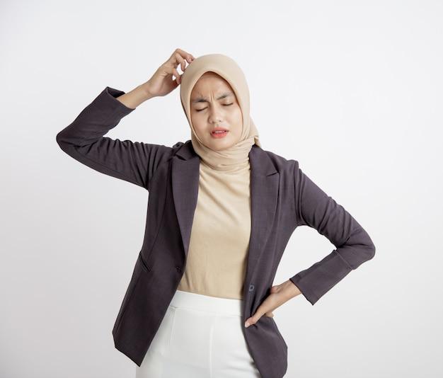 Mulher empresária usando hijab cansada hoje, segurando a cabeça e a mão na cintura, conceito de trabalho de escritório isolado