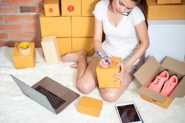 Mulher empresário proprietário pme negócios está verificando a ordem com smartphone, laptop e caixa de embalagem para enviar seu cliente