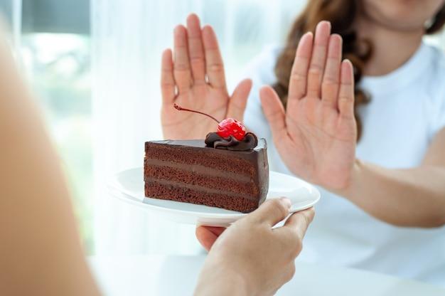 Mulher empurra o prato de bolo