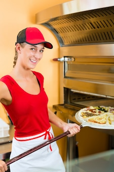 Mulher empurrando a pizza no forno