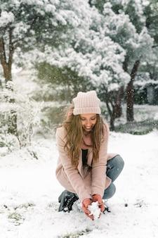 Mulher encantada com roupas quentes sentada em um bosque com um monte de neve e aproveitando o fim de semana no inverno