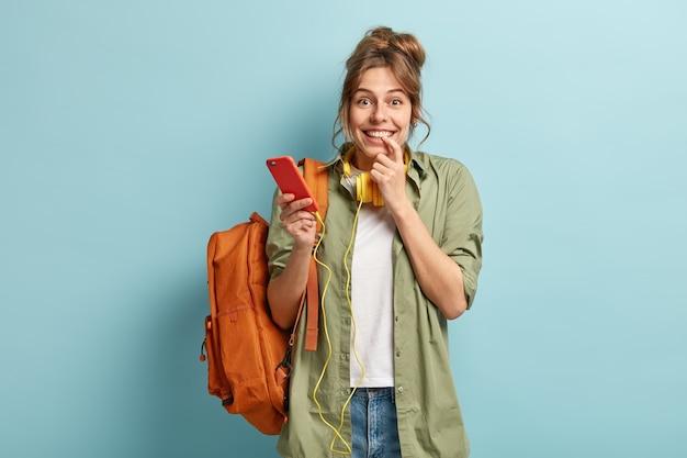 Mulher encantada e satisfeita ouve áudio em fones de ouvido eletrônicos, sente-se bem durante a comunicação online e tem tempo para ouvir suas músicas favoritas