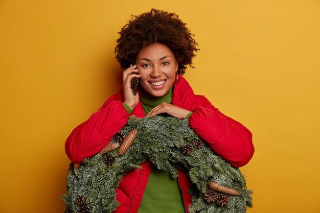 Mulher encantada liga pelo celular, tem clima de festa na véspera de natal, conta as últimas notícias, carrega coroa de abetos com pinhas, sorrisos amplamente isolados na parede amarela.