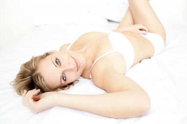 Mulher encantada relaxando deitada em sua cama