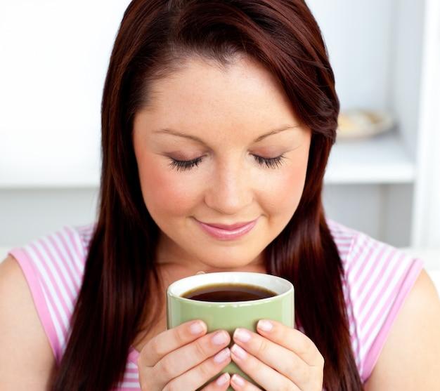 Mulher encantada segurando uma xícara de café em casa