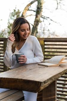 Mulher encantada sentada no terraço de madeira com um copo de bebida quente e lendo um livro, aproveitando o pôr do sol no verão, olhando para longe