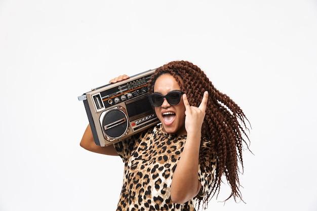 Mulher encantada, sorrindo e segurando uma caixa de som vintage com fita cassete no ombro, isolada contra uma parede branca