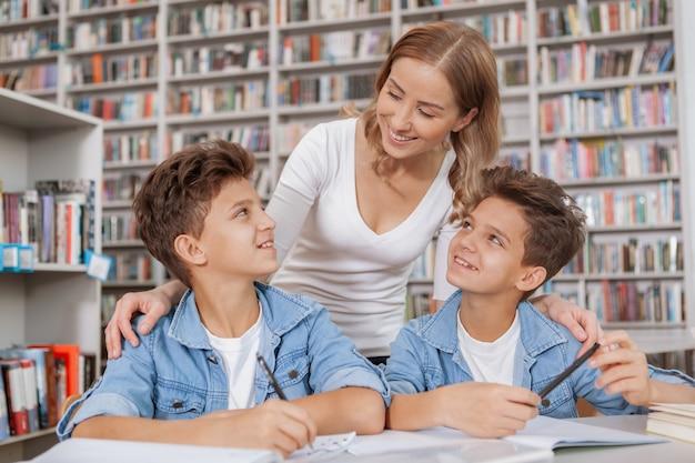 Mulher encantadora, ajudando seus filhos com a lição de casa na biblioteca.