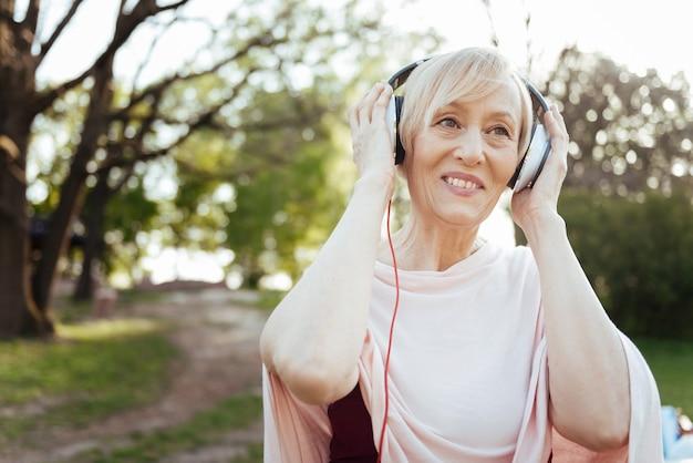 Mulher encantadora aposentada encantada usando fones de ouvido enquanto aproveita o tempo livre ao ar livre e ouve música