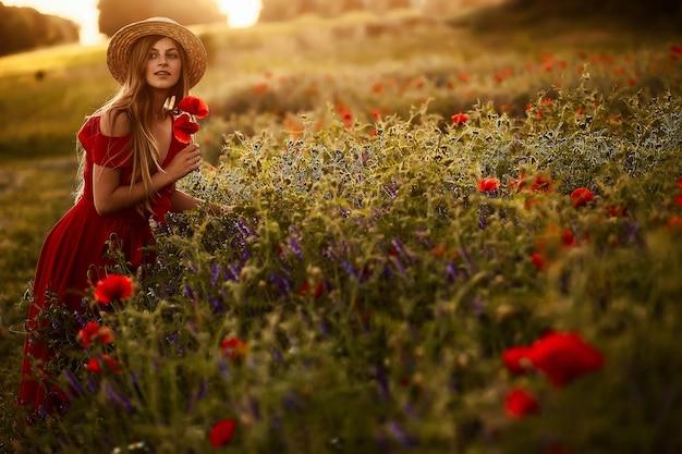 Mulher encantadora atravessa um campo verde com papoulas nos raios do sol da tarde