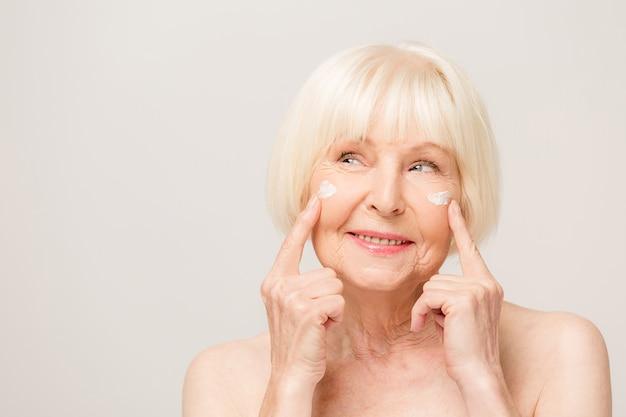 Mulher encantadora, bonita e velha tocando a pele macia e perfeita do rosto com os dedos, sorrindo para a câmera sobre fundo cinza, usando creme facial diurno e noturno, procedimentos de cosmetologia
