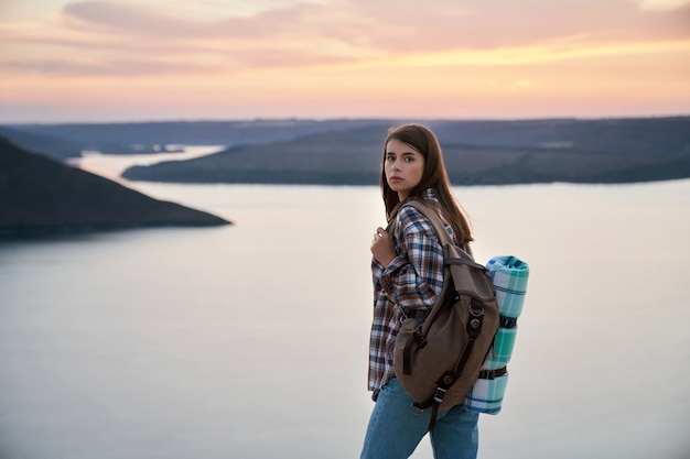 Mulher encantadora com cabelo castanho, olhando para a câmera em pé no alto do parque nacional podillya tovtry.
