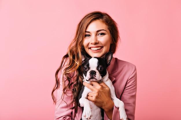 Mulher encantadora com cabelo ruivo brilhante, posando com seu animal de estimação. menina bem-humorada com jaqueta rosa segurando o cachorrinho.