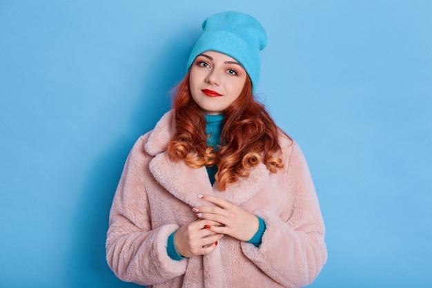 Mulher encantadora com cabelo vermelho, usa um elegante casaco de pele rosa e boné