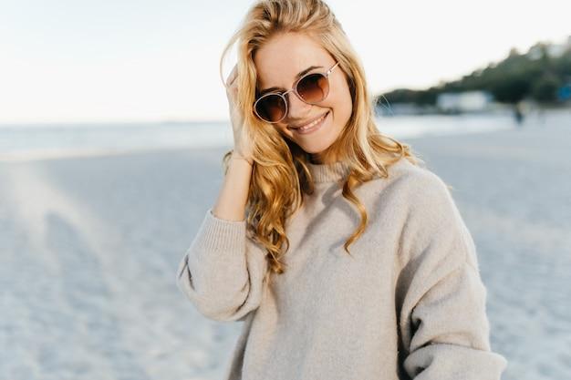 Mulher encantadora com cabelos cegos ondulados, vestida com blusa leve e óculos escuros com sorriso contra o mar.