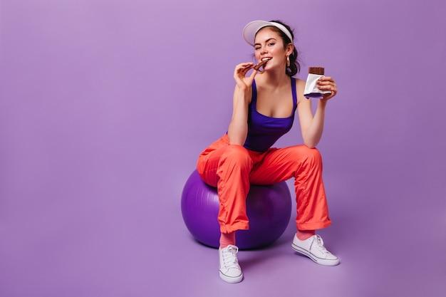 Mulher encantadora com calça de moletom laranja e blusa roxa está sentada no fitball comendo chocolate