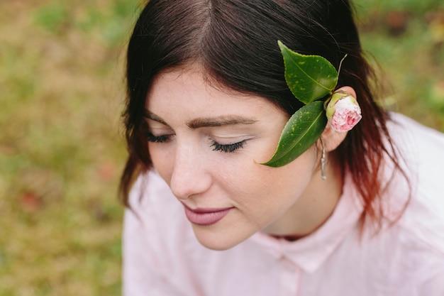 Mulher encantadora com flor e folhas no cabelo