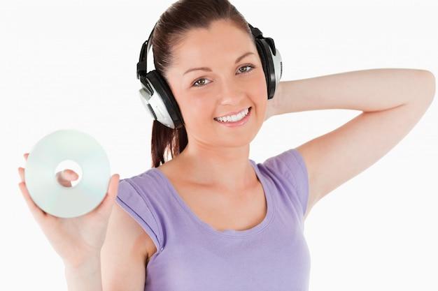 Mulher encantadora com fones de ouvido com um cd enquanto está de pé