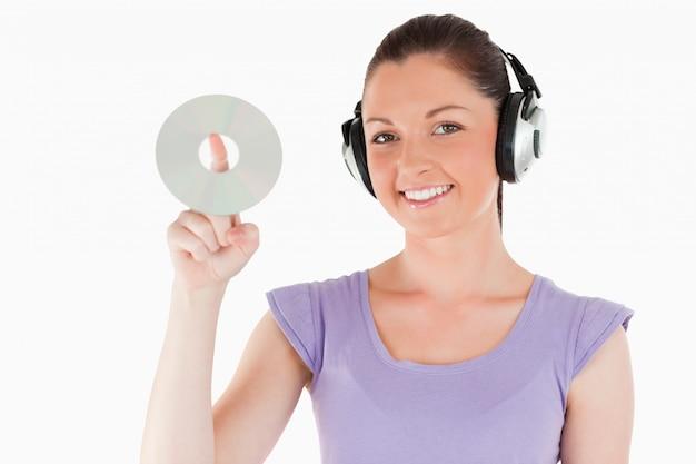 Mulher encantadora com fones de ouvido com um cd enquanto está em pé