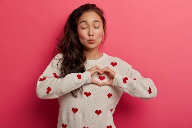 Mulher encantadora com lábios dobrados mostra um gesto de coração sobre o peito, expressa sentimentos comoventes, simpatia e ternura