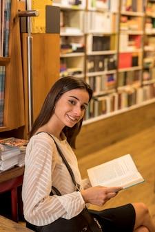Mulher encantadora com livro olhando para a câmera