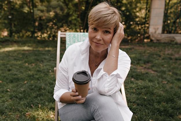 Mulher encantadora com penteado curto em jeans e camisa branca, segurando a xícara de café, olhando para a câmera e sentado no parque.