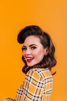 Mulher encantadora com penteado encaracolado, olhando por cima do ombro. garota pin-up sorridente de camisa quadriculada, posando em fundo amarelo.
