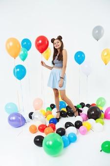 Mulher encantadora com penteado legal, segurando o balão de hélio vermelho