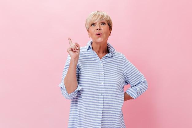 Mulher encantadora com roupa azul tem uma ideia e olha para a câmera no fundo rosa