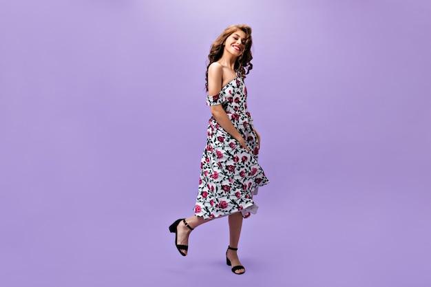 Mulher encantadora com roupa floral dançando no fundo roxo. linda garota encaracolada com cabelo comprido, posando para a câmera em pano de fundo isolado.