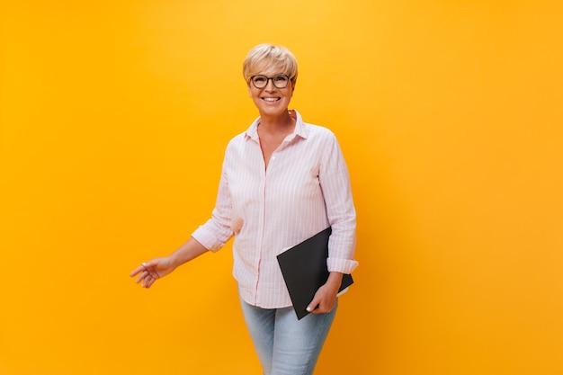 Mulher encantadora com roupa rosa e óculos posando com um tablet de papel
