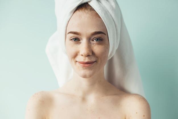Mulher encantadora com sardas sorrindo para a câmera com os ombros nus cobrindo a cabeça com uma toalha na parede de um estúdio