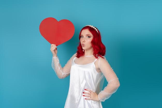 Mulher encantadora com um vestido branco e cabelo ruivo segurando um grande coração de papel vermelho e mandando um beijo